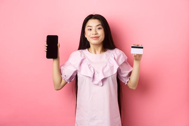 Allegra ragazza asiatica che mostra lo schermo vuoto dello smartphone e la carta di credito, acquisti online, in piedi su sfondo rosa.