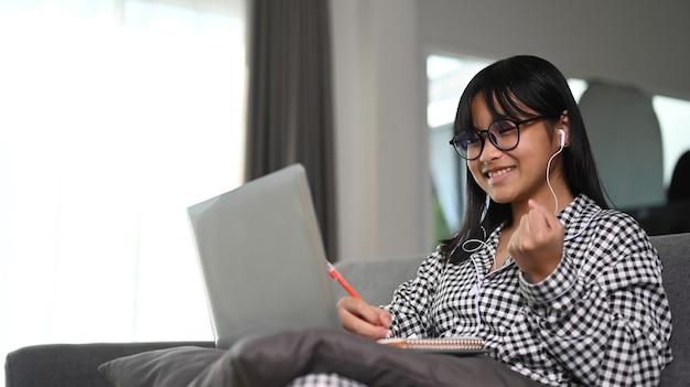 Studentessa asiatica allegra che utilizza il computer portatile per studiare online a casa.