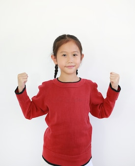 Bambina asiatica allegra che alza le mani per fare un gesto forte isolato su sfondo bianco. buon concetto di salute