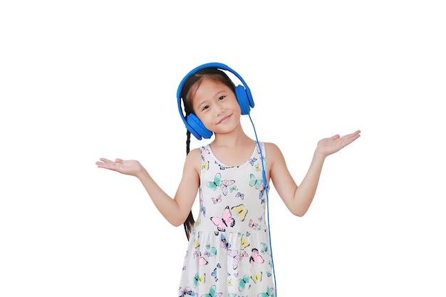 Ragazza asiatica allegra del bambino piccolo che indossa le cuffie blu e spalancate le mani isolate su priorità bassa bianca