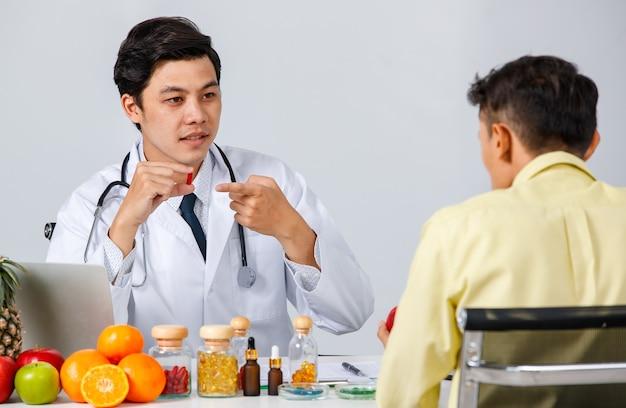 Allegro medico maschio asiatico e paziente seduti a tavola e parlando di pillole mentre si guardano durante l'appuntamento su sfondo bianco