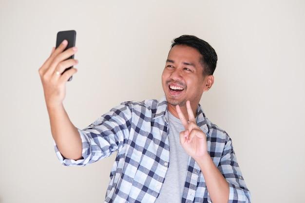 Uomo asiatico allegro che sorride felice mentre prende un selfie
