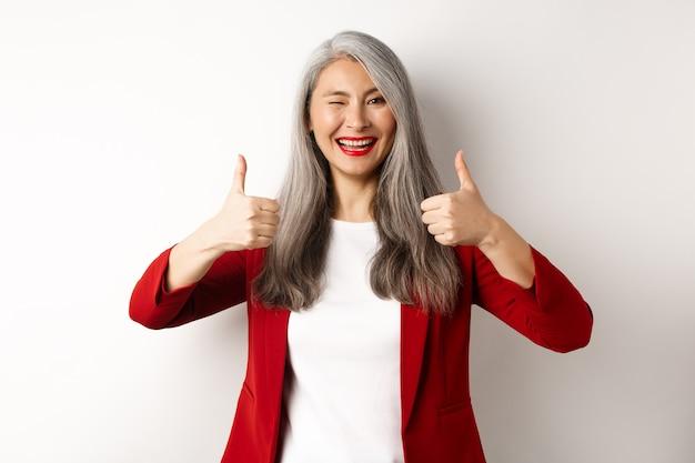Donna matura asiatica allegra che sbatte le palpebre, sorride compiaciuta e mostra i pollici in su in approvazione, gradisce e accetta, stando contro il fondo bianco.
