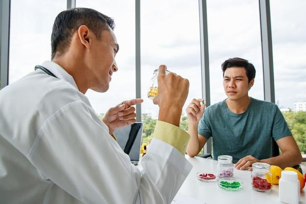 Allegro nutrizionista asiatico in uniforme medica che sorride e dimostra pillole di vitamine all'uomo mentre è seduto a tavola durante il lavoro in ospedale Foto Premium