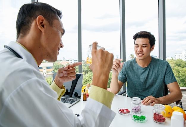 Allegro nutrizionista asiatico in uniforme medica che sorride e dimostra pillole di vitamine all'uomo mentre è seduto a tavola durante il lavoro in ospedale