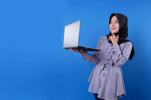 La donna asiatica allegra porta un computer portatile e un'espressione di pensiero