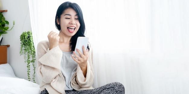 Allegra donna asiatica entusiasta di ricevere buone notizie mano che tiene il telefono cellulare felice e ride a letto