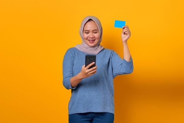 Donna asiatica allegra che tiene il telefono cellulare e mostra la carta di credito su sfondo giallo