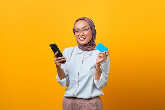 Donna asiatica allegra che tiene in mano uno smartphone e mostra una carta bianca su sfondo giallo