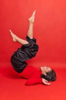 La donna asiatica allegra tiene le gambe sollevate cerca di fare in modo che le spalle si mettano in posa a piedi nudi indossa dolcevita e pantaloni neri esercizi dopo il lavoro isolato sul muro rosso essendo in buona forma