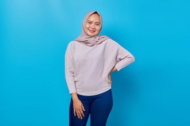 Donna asiatica allegra che guarda l'obbiettivo su sfondo blu