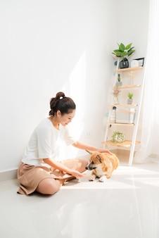 Donna asiatica allegra che gioca con il suo cane corgi