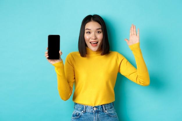 Donna asiatica allegra che mostra lo schermo vuoto dello smartphone e alza la mano per salutarti, salutarti, in piedi su sfondo blu.