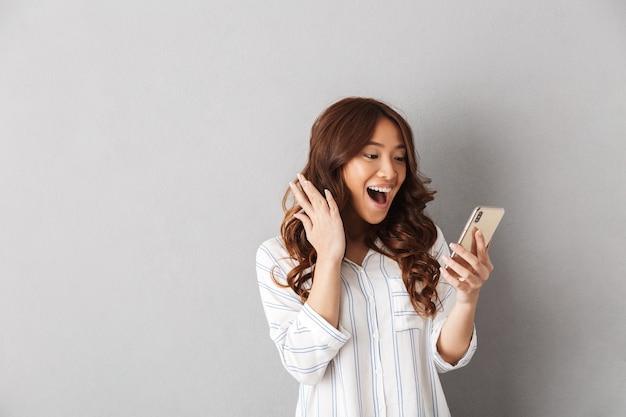 Allegra donna asiatica in piedi isolato, tenendo il telefono cellulare, celebrando