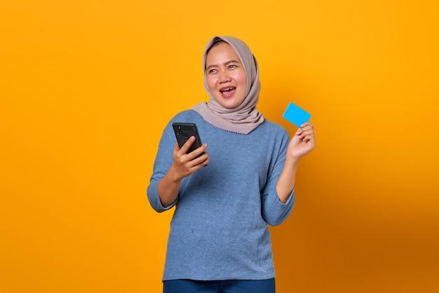 Allegra attraente donna asiatica che tiene il telefono cellulare e mostra la carta di credito su sfondo giallo