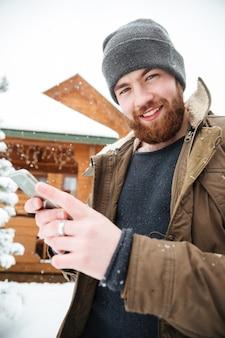 Uomo barbuto allegro e attraente che utilizza phpne mobile in piedi di fronte alla cabina di tronchi in inverno
