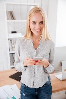 Donna d'affari allegra e attraente che usa il telefono cellulare in ufficio e guarda davanti