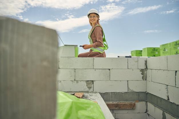 Allegro attraente direttore di costruzione con un telefono cellulare in mano seduto sulla muratura