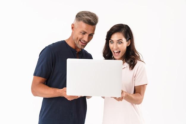 Allegra coppia attraente che indossa un abito casual in piedi isolato su un muro bianco, con in mano un computer portatile