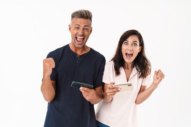 Allegra coppia attraente che indossa un abito casual in piedi isolato su un muro bianco, giocando sui telefoni cellulari, celebrando il successo