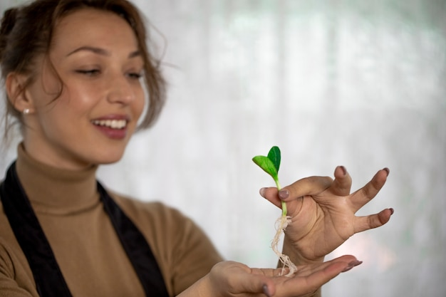 Ragazza attraente allegra con il germoglio del fiore della tenuta di sorriso prima della piantatura dell'interno