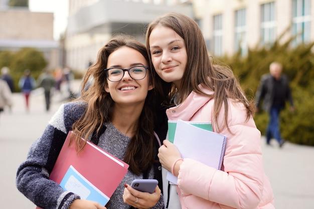 Studenti allegri ragazze attraenti che tornano a casa dopo la classe all'università