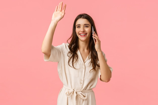 Donna caucasica sorridente attraente allegra vedendo amico e salutando, salutando come parlando al telefono, parlando, chiamando qualcuno con conversazione e saluto passante, muro rosa