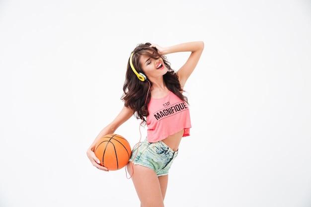 Donna attraente allegra che tiene la palla da basket e ascolta musica in cuffia isolata