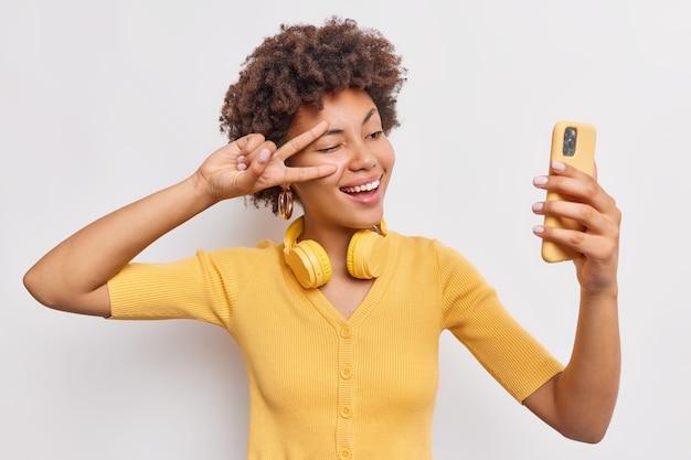 La donna attraente allegra con i capelli afro fa sefie registra video su smartphone fa gesto di pace su supporti per gli occhi felice utilizza le moderne tecnologie per l'intrattenimento isolato sul muro bianco dello studio