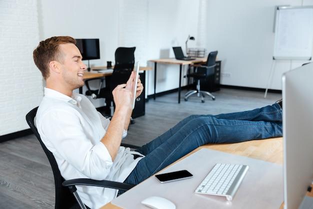 Giovane uomo d'affari allegro e attraente seduto con le gambe sul tavolo e usa il tablet in ufficio