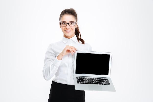Giovane donna di affari attraente allegra in vetri che tengono il computer portatile dello schermo in bianco sopra la parete bianca