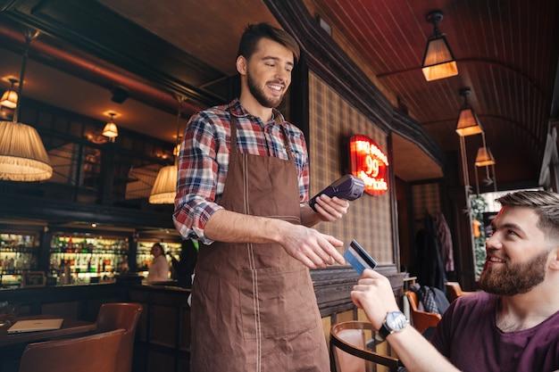 Giovane attraente allegro seduto al bar e pagando il conto con carta di credito