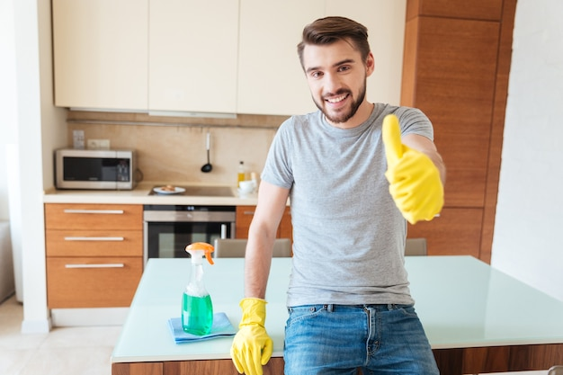 Un giovane allegro e attraente con guanti di gomma gialli che pulisce il suo appartamento e mostra i pollici in su