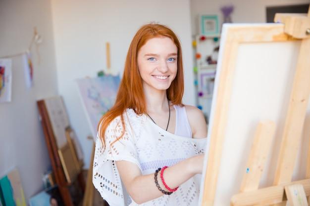 Artista allegro e attraente della giovane donna che dipinge su tela in