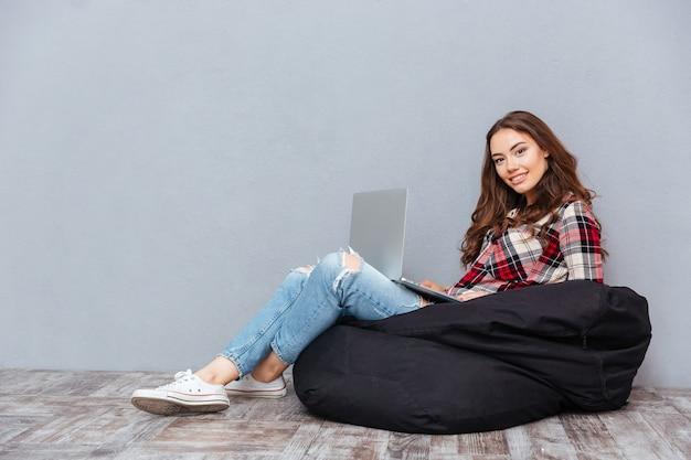 Giovane donna attraente allegra che si siede e che usa il computer portatile sul sacchetto di fagioli neri