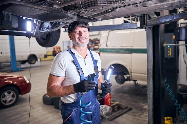 Allegro meccanico in piedi sotto l'auto sollevata in garage