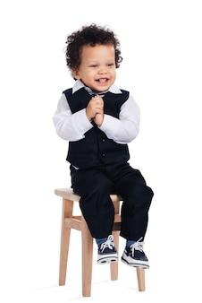 Neonato allegro. piccolo neonato africano che guarda lontano con un sorriso mentre è seduto su uno sgabello su sfondo bianco