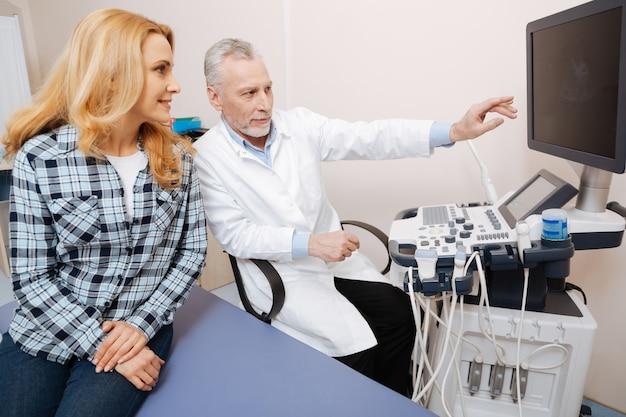 Medico esperto barbuto allegro che lavora in ospedale e consulta il paziente mentre fornisce l'esame ecografico del corpo