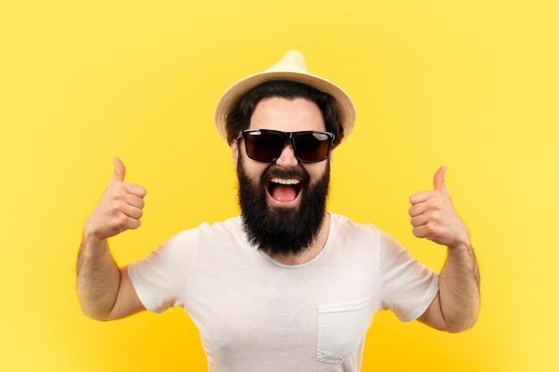 Allegro ragazzo barbuto in occhiali da sole e cappello di panama, mostra come