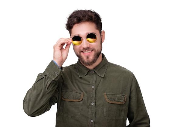 Ragazzo barbuto allegro che tocca il telaio degli occhiali da sole, in piedi su sfondo bianco isolato