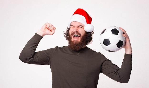 Allegro barbuto hipster uomo che grida e celebra la vittoria e tiene il pallone da calcio, babbo natale