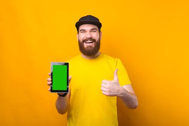 Uomo barbuto allegro hipster che mostra schermo verde su tablet e pollice in su