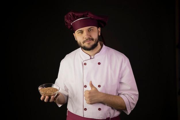 Il cuoco unico maschio barbuto allegro in ciotola uniforme della tenuta di cereali mostra i pollici in su