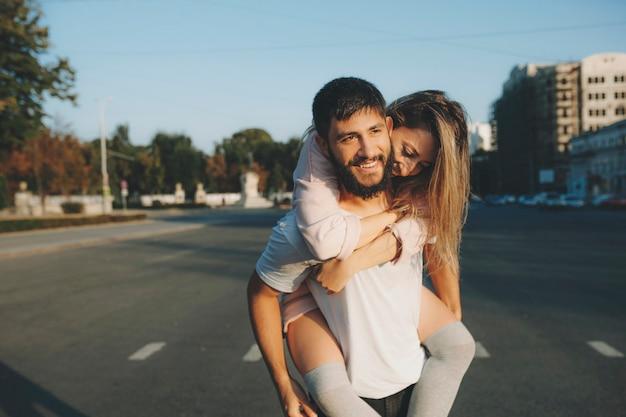 Allegro uomo barbuto che porta la giovane donna sulla schiena mentre si cammina per strada nel tempo libero