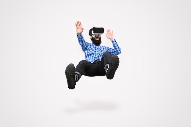 Allegro uomo barbuto in occhiali realtà virtuale levitante su sfondo grigio