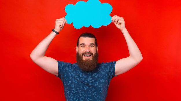 Uomo barbuto allegro che tiene nuvola blu vuota su sfondo rosso red