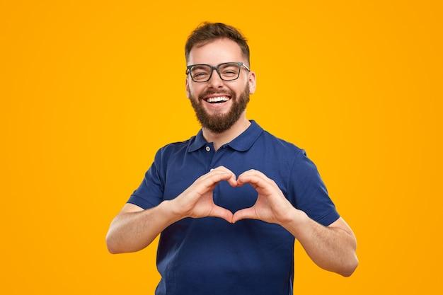 Allegro uomo barbuto che mostra il gesto del cuore