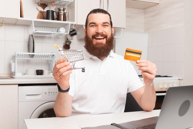 Allegro uomo barbuto sorridente e tenendo il carrello della spesa e la carta di credito davanti al computer portatile