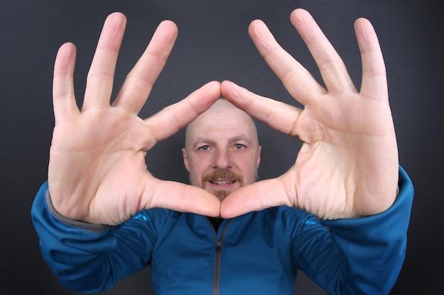 Allegro uomo barbuto con le mani in alto