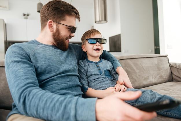 Allegro giovane padre barbuto che tiene il telecomando mentre guarda la tv con il suo piccolo figlio carino usando occhiali 3d.
